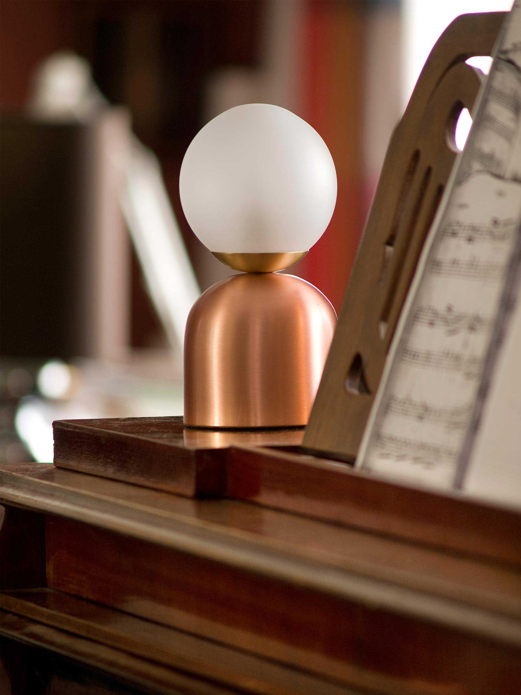 BONBON COPPER LIGHT Lovely petite Bonbon Table Lamp in copper material emanates a soft glow from a carefully spun metal structure and hand-blown glass diffuser.